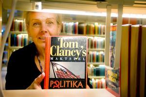 Biblioteksassistenten Lena Eriksson visar upp en av bibliotekets många Tom Clancy-böcker. Hon tycker det är roligt att Söderhamn är med i den nya boken.