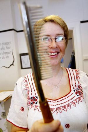 Åse visar en elektrisk kam som användes för att skapa vågor i håret.