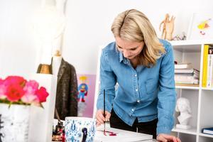 Carina målar på sitt kontor i Falun.
