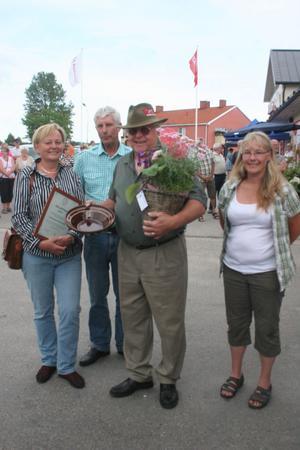 Pristagarna Åsa Wassberg med diplomet och Björn Englund med blomsterkorgen har harangerats av juryrepresentanterna Pernilla Kardell och Stig Eng.