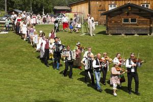Rankan bäres fram av barnen och Ljusdals Folkdanslag med spelmännen i spetsen.   Foto: Yngve Karlsson