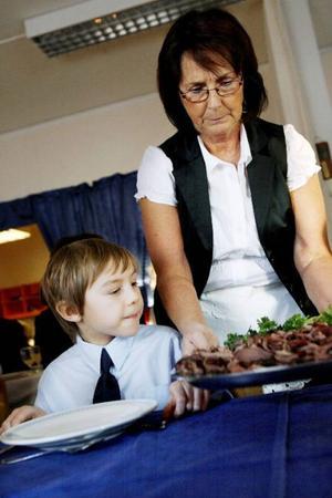 Läraren Anita Vold serverar Magnus Gärdin i tvåan några skivor nötsstek till varmrätten.