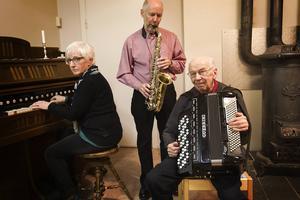 Ami Andersson, Gunnar och Uno Jonsson spelar i eldstadens värme.