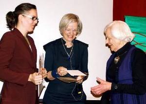 Johanna Grinde, till vänster, mottar stipendiet av Görel Åsbo-Stephansson, ordförande i JLK. Till höger ses Ingrid Engelfeldt som har stiftat stipendiet.