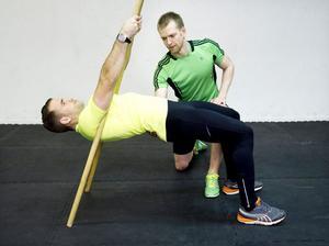 2. Liggande ryggrad med käppStå med käpparna framför dig som i övning ett. Gå framåt samtidigt som du lutar dig bakåt tills du blir liggande med kroppen i linje med golvet med sträckta armar. Dra dig upp så att axlarna nuddar händerna.Du tränar: Axlarnas baksida, biceps (armens framsida), ryggen, rumpan.