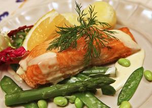 Ugnsstekt lax med gröna tillbehör och en mild sås spetsad med mild vinäger är passande påskmat.