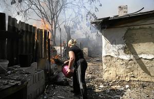Sönderbombat hus. En kvinna i Donetsk i östra Ukraina försöker släcka elden genom att hälla vatten från en hink på de brinnande resterna. Arkivfoto: Sergei Grits/ TT