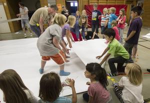 Barnen måste hjälpas åt för att lyckas vika det stora pappersarket.