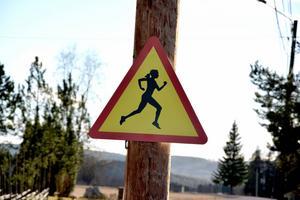 En skylt som signalerar att det finns löpare utefter vägen.