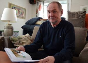 Lars Andersson tittar i boken som personalen på IVA gjorde åt honom under sjukhusvistelsen.