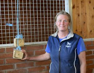 """Lena Erkers visar ett par av de för hästarna intressanta """"leksaker"""" som personal och elever utvecklade för att ge hästarna en lugn sinnesupplevelse och få dem att trivas. Det är föremål som luktar, låter eller på annat sätt kan berika hästarnas tillvaro under den tid de är sjuka och tillfrisknar."""