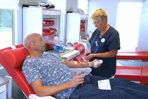 Lisbeth Forslund, sjuksköterska, hjälper blodgivaren Fredrik Oliwsson till rätta i britsen i blodbussen.
