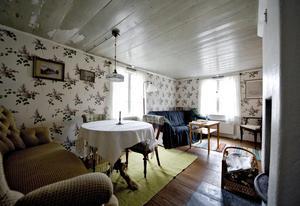 Allrummet på bottenvåningen har fått nya, somriga tapeter och den gamla svagt gröna takfärgen skrapades fram. Möblerna och trasmattorna är hämtade från förr.