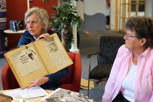 Ingrid Landgren visar upp gamla tidningsartiklar. Till höger är Maud Eriksson.