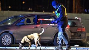 De beskjutna satt i bilen till vänster i bild bakom polisen med polishund. Bilen besköts med 17 skott. Bild: Claudio Bresciani/TT