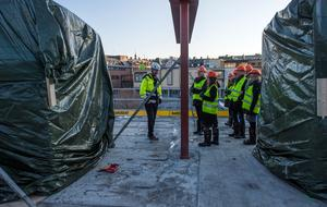 Patrik Backlund och resten av gruppen på varsin sida av stålbalken som visar var väggen mellan de två hotellrummen på våning två kommer att vara.