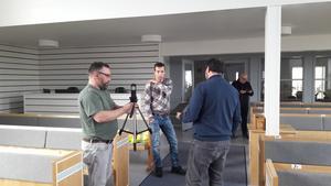Niclas Hugosson, Jochem van Dijk och församlingens pastor Mattias Bjurenholt samtalar om inspelningsteknik för påskvandringen. Foto: Gunnar Nimmersjö