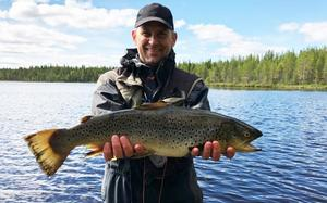 Martin Nilsson visar upp sin öring som han fångade i Rörsjön, Hedeviken.