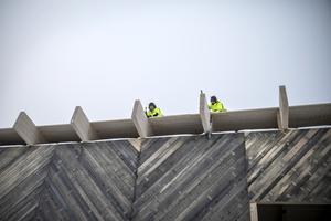 Allt byggjobb görs på egen hand och med en hel del eget virke. Här sätter Leo Wallner och Rasmus Dahlberg de sista raderna av spontat virke på taket.