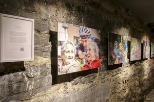I Lux källarlika utställningslokal hänger bilder från nio länsbors vardag och på en skärm visas filmer där var och en av dem motiverar deras val att bo i Jämtlands län.