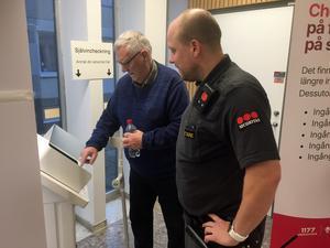 Väktaren Tommy Sarlin hjälper Jan Olsson med självincheckningen.
