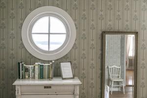 Ett runt fönster i gästrummet med utsikt över Storsjön och den Jämtländska fjällvärlden.
