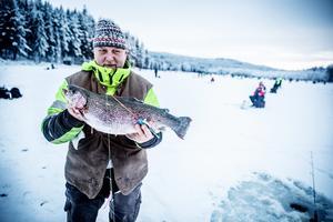 Jan visar upp fisken, och det lilla, lilla spö som han fångade den med.