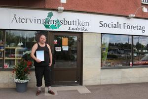 Kim Persson med diplomet i handen utanför Återvinningsbutiken i centrala Ludvika. Återvinningsbutiken är en second handbutik som anställer personer för att de ska få ett jobb och hitta in i samhället igen.