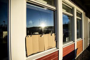 En del krossade fönster har täckts över med kartong i väntan på att bytas ut.