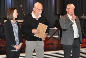 Gustav Erikson utsågs till Årets Grynkorvsstipendiat. Här tar hans hustru Ann emot utmärkelsen av Leif Mannerström. Fjälstret Tommy Kroon läser upp motiveringen.