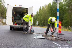 Vägarbetare fräser bort asfalt där de ska sätta ner fästet för mitträcket.