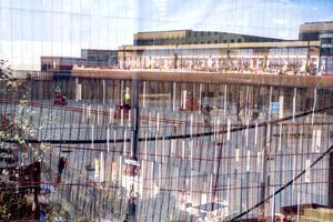 Ett tunt tyg med en bild av hur hotellet kommer se ut hänger på staketet.Igenom syns arbetet med att gjuta den första plattan.