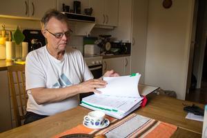Kjell Jansson bläddrar i pärmen med kvitton han sparar för sitt arbete som god man.