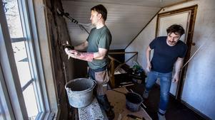 Boris hjälper Darius Andrulevicius som applicerar lera på väggarna.
