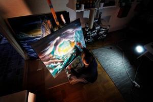 Benny Halldin framför sin senaste tavla där han använder en airbrush för att göra vissa partier ljusare så att de verkar självlysande.