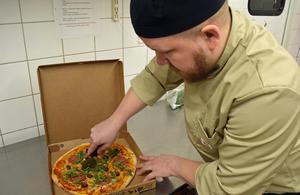Björn Olli, en av pizzabagarna, tar hand om en av dagens beställningar