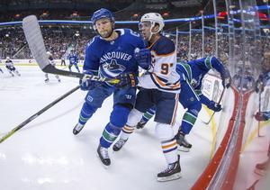 Edler i en närkamp med Edmonton Oilers 22-åriga superstjärna Connor McDavid, av många ansedd som den bästa spelaren i hela världen. Foto: Darryl Dyck/The Canadian Press