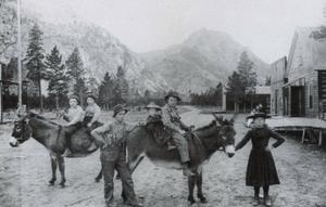 Vardagsliv i Frisco. Några barn rider på åsnor längs huvudgatan och i bakgrunden syns bergen där deras fädrer slet i gruvorna. I Frisco fanns vid den här tiden två livsmedelsaffärer, två hotell, tre salooner, två resestall, tre smeder samt mängder av andra affärsrörelser.