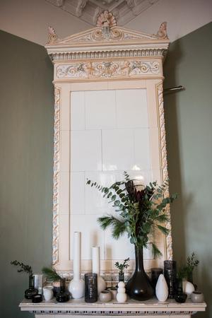 Kakelugnen har dekorerats med vaser med kvistar och blad i olika höjder.