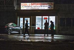 Poliser utanför lokalen där en person enligt vittnen sköts med två skott i benen.