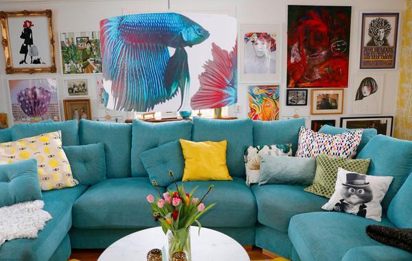 Den stora turkosa soffan står mitt i vardagsrummet och har plats för hela familjen.