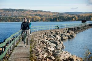 Martin och Sara cykalr på bryggan i Hjulbäck. Bryggan - Siljans längsta bybrygga -  började byggas redan under 1800-talet.