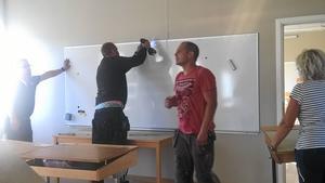 Här sätts en whiteboard tillbaka i klassrummet där den satt förut.