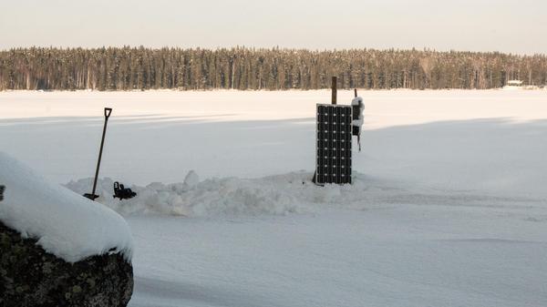 En ensam solpanel sticker upp där sommarsolen ska ge el åt Rogers elektriska båtmotor när snön och isen försvunnit.