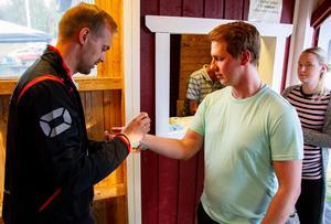 Niklas Persson spelar fotboll i Järvsö BK:s herrlag. Här stämplar han  Simon Jonassons hand. Simon har rest från Bollnäs till årets logdanspremiär.