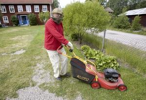 hatten är ett måste. Hilding Burman klipper gräset till sommarhuset i Österfärnebo.  Foto: Lars Nyqvist