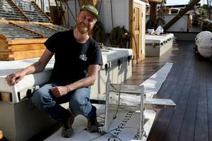 Marinbiolog Maarten Erich från Nederländerna. Här sittandes bredvid maskinen som samlar upp mikroplaster ur havet när stickproven genomförs. Maskinen dras efter vattenytan och de plastbitar som samlas upp fastnar längst bak i maskinens svans.