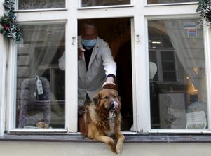 En munskyddsförsedd man klappar en hund som får lite frisk luft i Prag, Tjeckien.