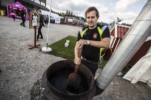 Jon Gustafsson blandar svart Falu rödfärg. Han berättar att den innehåller vatten, mjöl, pigment, gamla rester från Falu gruva, linolja och såpa.