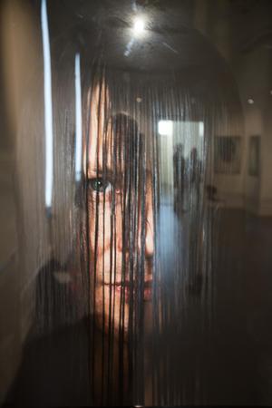 Konsthallen speglas i bilden av Janna, med det långa våta håret kammat till en skyddande gardin.